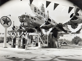 Old photograph showing the Bomber Gas Station, with a frontal view of the B-17 bomber above the gas pumps. To the side is a sign saying Texaco.
