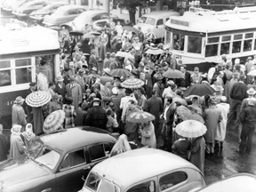 Old photograph showing many pedestrians, some with umbrellas, in Oak Grove. Some are getting on and off of two trolleys. Several cars are parked.