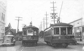 Old photograph showing two trolleys passing on a street.